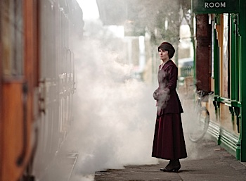 woman outside train station near steam engine