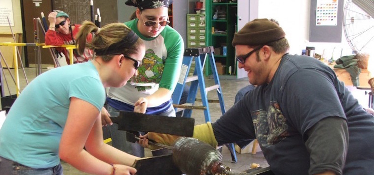 Students Brandi Hunt, left, and Tori Niemeier help instructor Brian Alloway work a piece of glass during class at Hocking College. (Arian Smedley/The Athens Messenger)