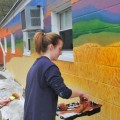 Ohio University students Momo Liu and Meg Beerse work on the new mural outside the Athens Bread Company on East State Street. (John Halley/Athens Messenger)