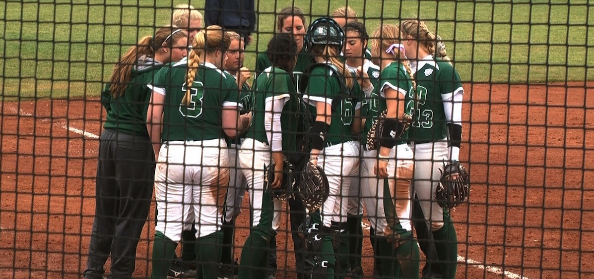 OU softball team meeting on third base line