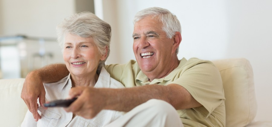 Elderly people sitting on a couch, smiling