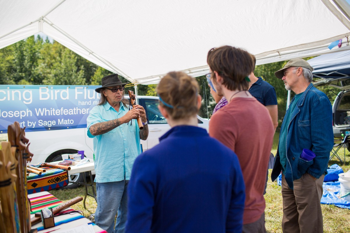 A crowd gathers as Joseph Whitefeather explains the process of making his handcarved flutes. ( Jasmine Beaubien/WOUB)