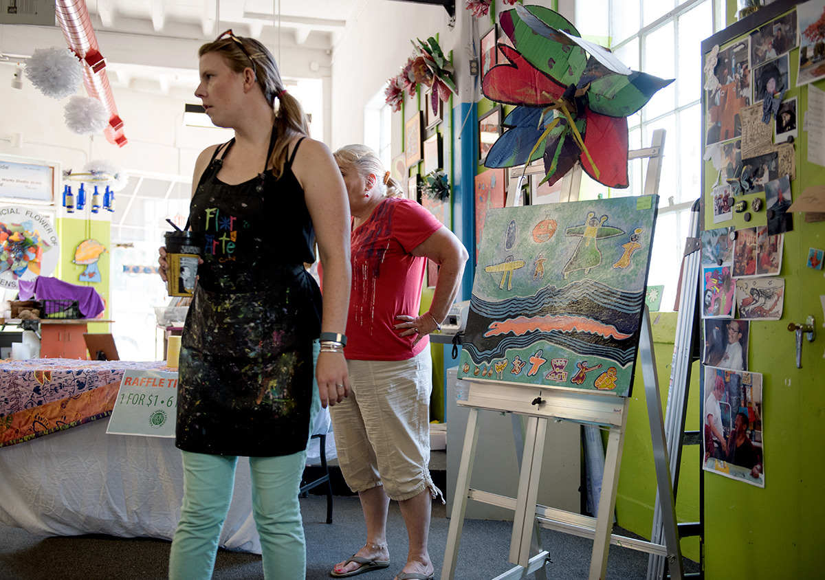 (Left) Mallory Vallentour and Laurie Gregg look in on the Passion Works Studio as customers file on during their summer bash event. Vallentour is a staff artist and retail representive while Gregg is the studio director. In the summer bash held on Saturday, Sept. 19, 2015, Passion Works had their clients, many with disabilites come in to paint work, mostly makeshift blocks on cardboard to display at the Homecoming parade later this year. (Jeffrey Zide/WOUB)