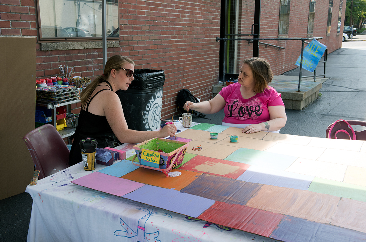 Mallory Valentour(left) works with Marilyn Tucker(right) on painting makeshift bricks on cardboard during the Passion Works Summer Bash at the Passion Works Studio in Athens, Ohio on Saturday, September 19, 2015. The makeshift bricks will be displayed at the homecoming parade later this year.