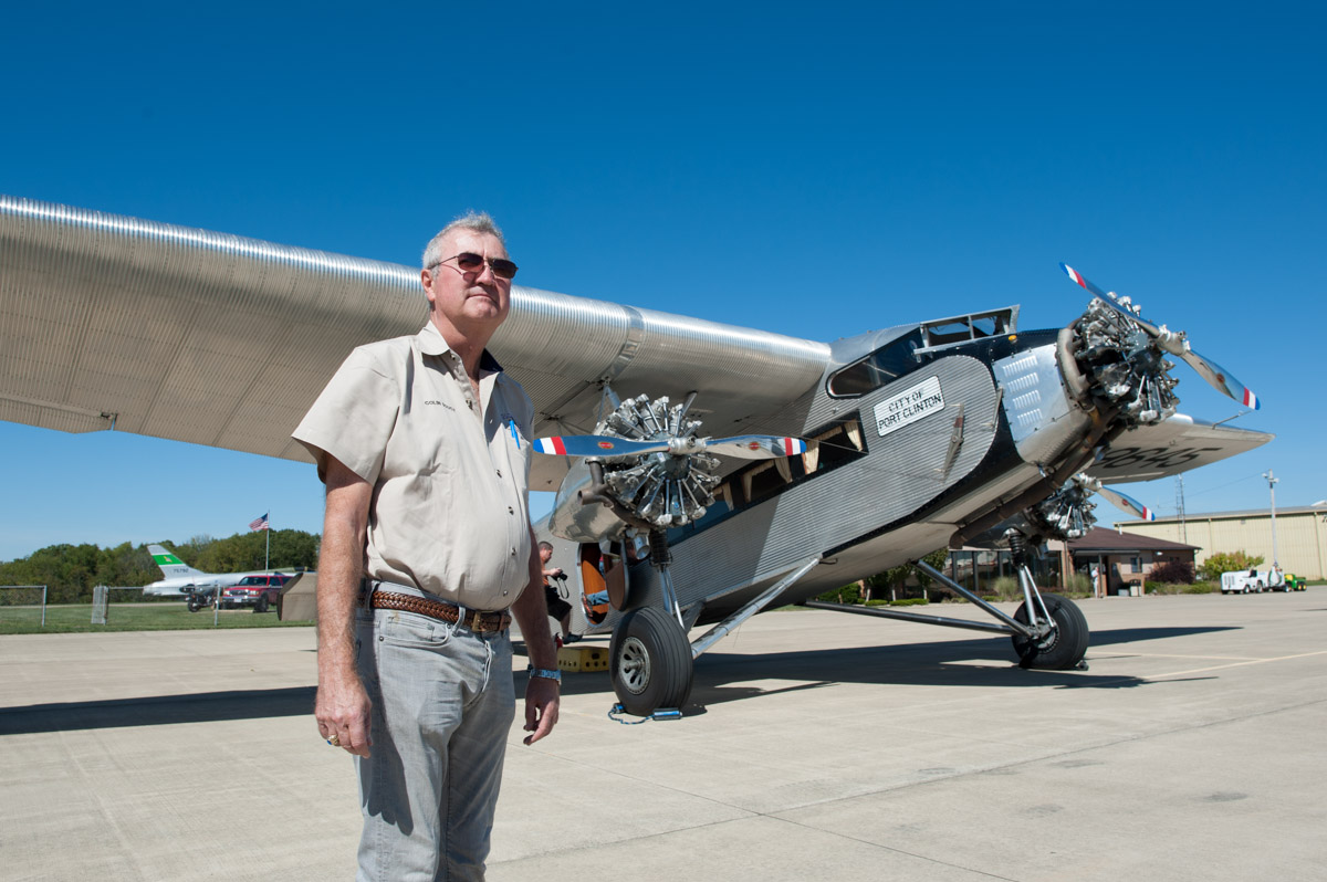"""Captain Colin Soucy poses for a portrait in front of a 1928 Ford Tri-Motor, one of the world's first mass-produced airliners, at the Zaneville Municipal Airport in Zanesville, Ohio, on Thursday, Sept. 24, 2015. On loan from the Liberty Aviation Museum of Port Clinton, Ohio, to the Experimental Aircraft Association, the aircraft, nicknamed the """"Tin Goose,"""" is touring throughout the United States. The public will be able to ride in the """"Tin Goose"""" at the Zanesville Municipal Airport 9 a.m. to 5 p.m. this Thursday to Sunday. (Yi-Ke Peng/WOUB)"""