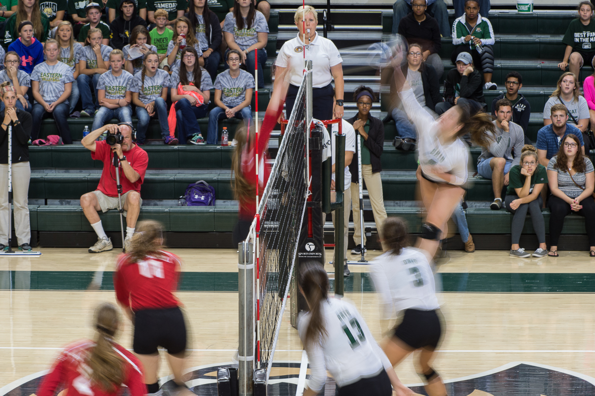 """OU middle blocker Ali Lake (#8, top right) spikes the ball against arch rival Miami in a """"Battle of the Bricks"""" showdown at the Convocation Center in Athens, Ohio on Saturday, September 26, 2015. Lake had seven kills total while only having one attack error in 21 attempts. The Bobcats defeated the RedHawks 3-1 (25-20, 25-16, 25-27, 25-20). (Nicole Raucheisen/WOUB)"""