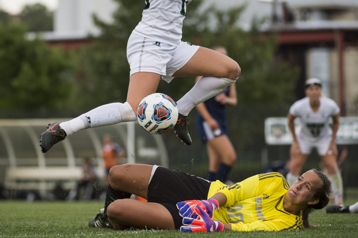 Robert Morris goal keeper Chelsea de Jager (#00) slides to block the ball from her Ohio University opponent Allie Curry at Chessa Field in Athens, Ohio on Friday, September 11, 2015. Ohio University shutout Robert Morris University 3-0.
