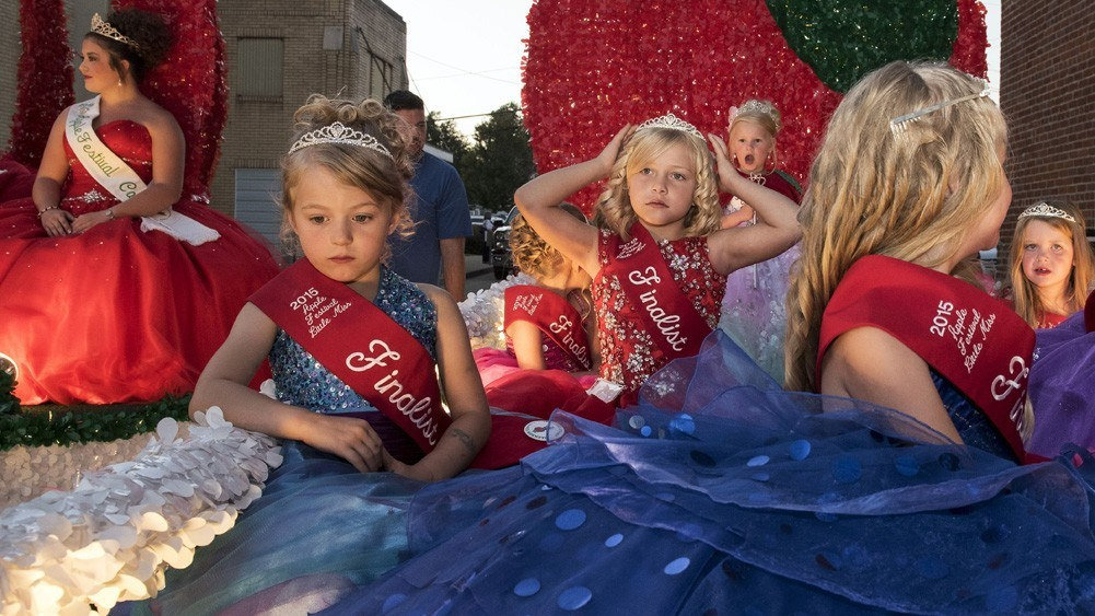The Little Miss Apple Festival Queen, Noel Saunders, and finalists await the start of the Seventy-fifth Annual 2015 Apple Festival Parade on Wednesday evening, September 23, 2015. (Left) Katlyn Yerian, Emily Gardner, Chloe Young, Queen Noel Saunders, Amarybee McCain, and Jolee Miller. (Margaret Sabec/WOUB)