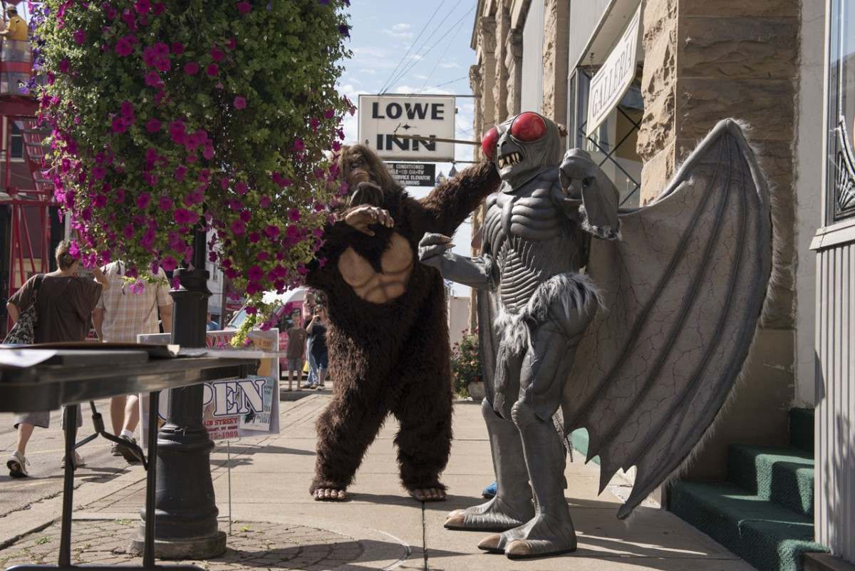 Local character actors Garrett McGuire, as Bigfoot, and Joss Hayman, as the Mothman, put on their best poses in front of the Lowe Inn during the Mothman Festival. (Margaret Sabec/WOUB)