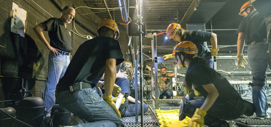 Jeff Russell (far left), director of the SHAPe Clinic, and Lowell Jacobs (background center), master electrician with School of Theater, guide students through emergency response procedures in the Forum Theater's lighting grid. (Matthew Forsythe)