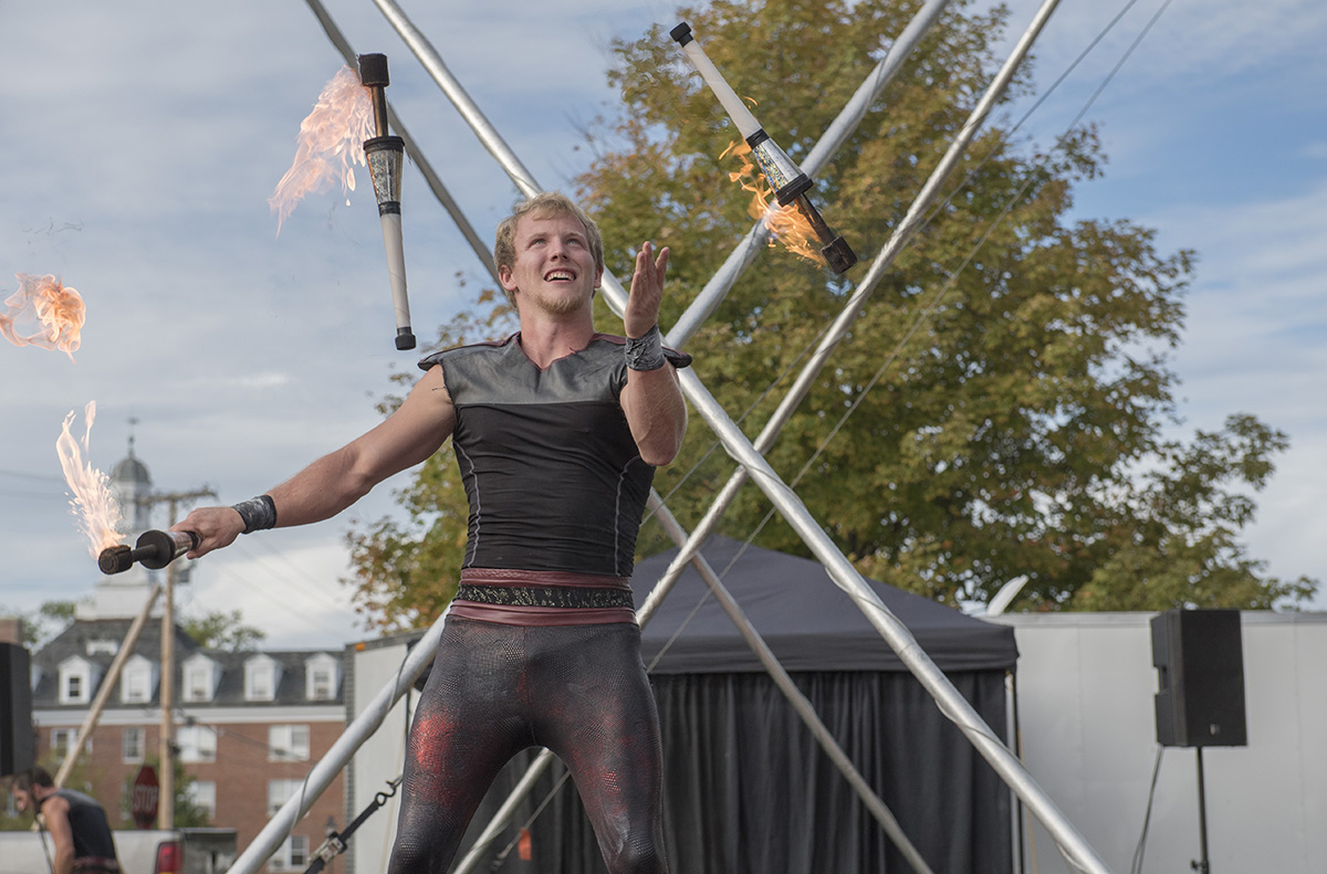 A performer from the Cincinatti Circus juggles three bowling pins lit with fire at Cirque du Ohio on South Green on Tuesday Oct. 6, 2015. (Jeffrey Zide / WOUB)