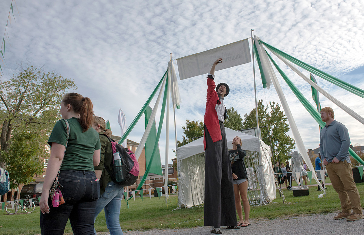 A man on giant stilts from the Cincinatti Circus takes a selfie with a student at Cirque du Ohio on the South Green on Oct. 6, 2015. (Jeffrey Zide / WOUB)