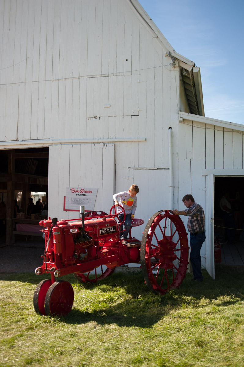 Mason Blackburn, 6, of Waverly, Ohio, plays on a tractor while his dad James Blackburn watches at the 45th annual Bob Evans Farm Festival at the Bob Evans Farm in Rio Grande, Ohio, on Sunday, Oct. 11, 2015. (Yi-Ke Peng/WOUB)