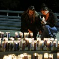 Meriah Calvert, left, of Roseburg, Ore., and an unidentified woman pray by candles spelling out the initials for Umpqua Community College after a candlelight vigil Thursday, Oct. 1, 2015, in Roseburg, Ore. A man opened fire at the school before dying in a shootout with police. (AP Photo/John Locher)