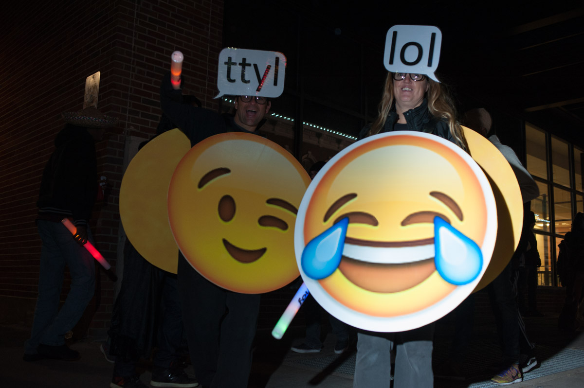 Bill and Lynda Harris pose for a portrait wearing their emoji costumes for the Halloween block party on Court St. in Athens, Ohio, on Saturday, October 31, 2015. (Yi-Ke Peng/WOUB)