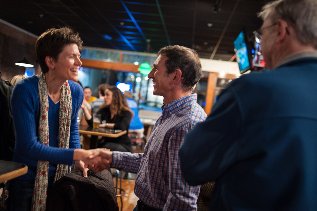 Jennifer Cochran shakes hands with Peter Kotses in the Pigskin in Athens, Ohio, after both were elected to Athens City Council at large on Tuesday, Nov. 3, 2015. (Yi-Ke Peng/WOUB)