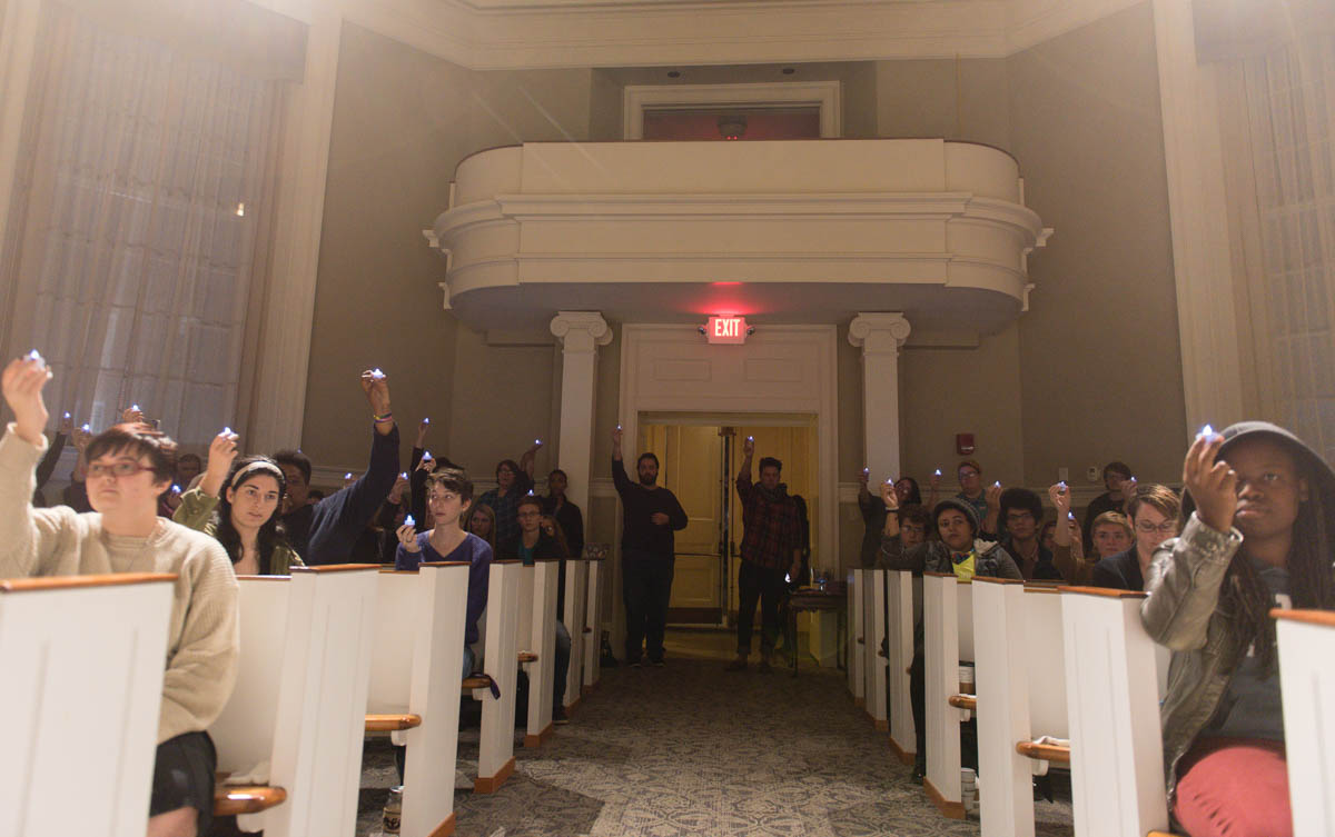 People hold up a tea lights used as candles after all the names of the transgender people who died this were read at the Transgender Day of Remebrance Vigil on Nov. 19, 2015.