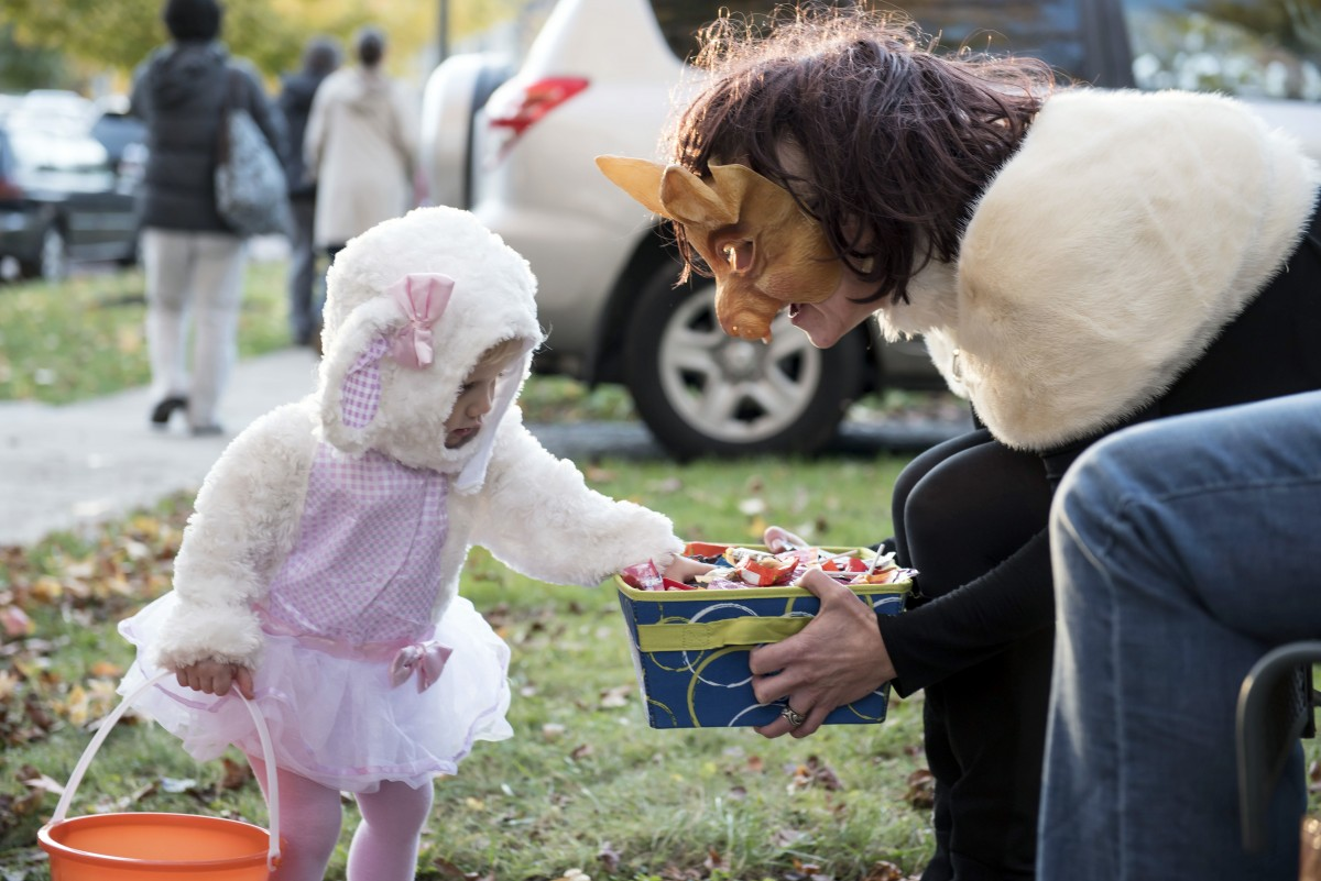 Blythe Kermode of Athens, carefully chooses her treats from the outstretched hands of Misha Finney on Beggars Night in Athens, Ohio on Thursday night, October 29, 2015. (Margaret Sabec / WOUB)