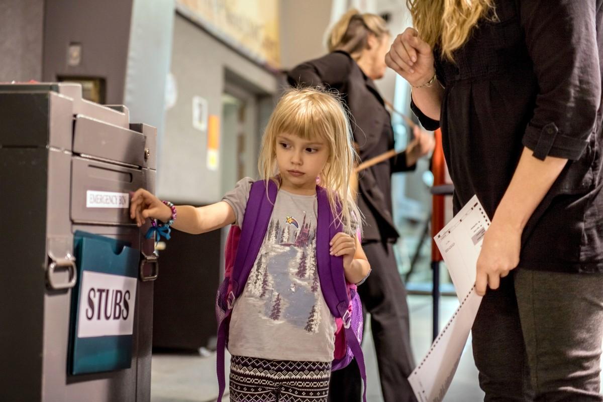 Violet Lehman, 4, helps her mother Elizabeth Lehman deposit her voting ballot at the Plains United Methodist Church, in The Plains, Ohio. Margaret Sabec/WOUB