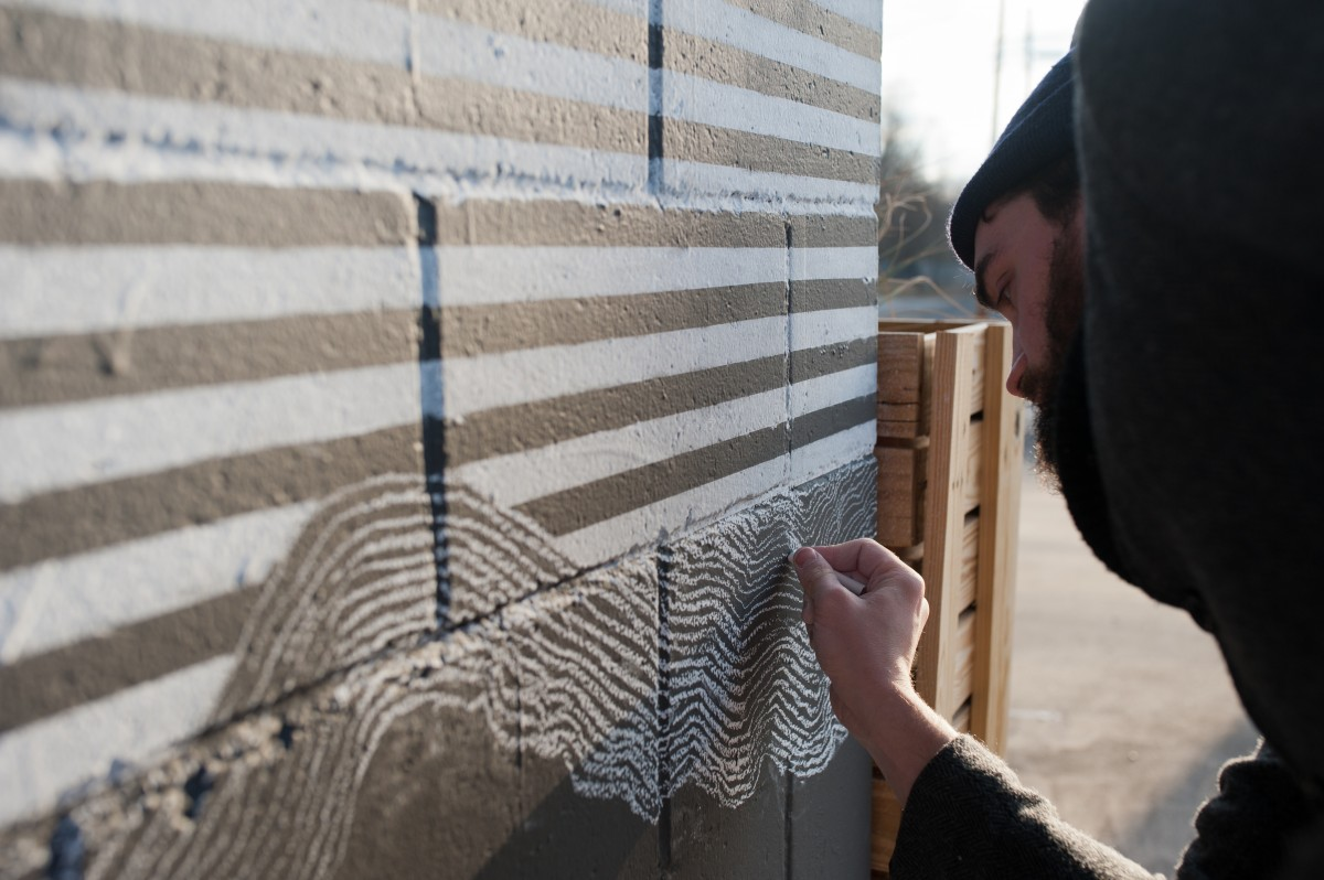 Andrew Clavin works on a chalk mural on the outside of OMG! Rotisserie on Columbus Rd. in Athens, Ohio on Sunday, Feb. 7. The mural took over 12 hours to complete using only tape and white chalk. (Mark Clavin/WOUB)