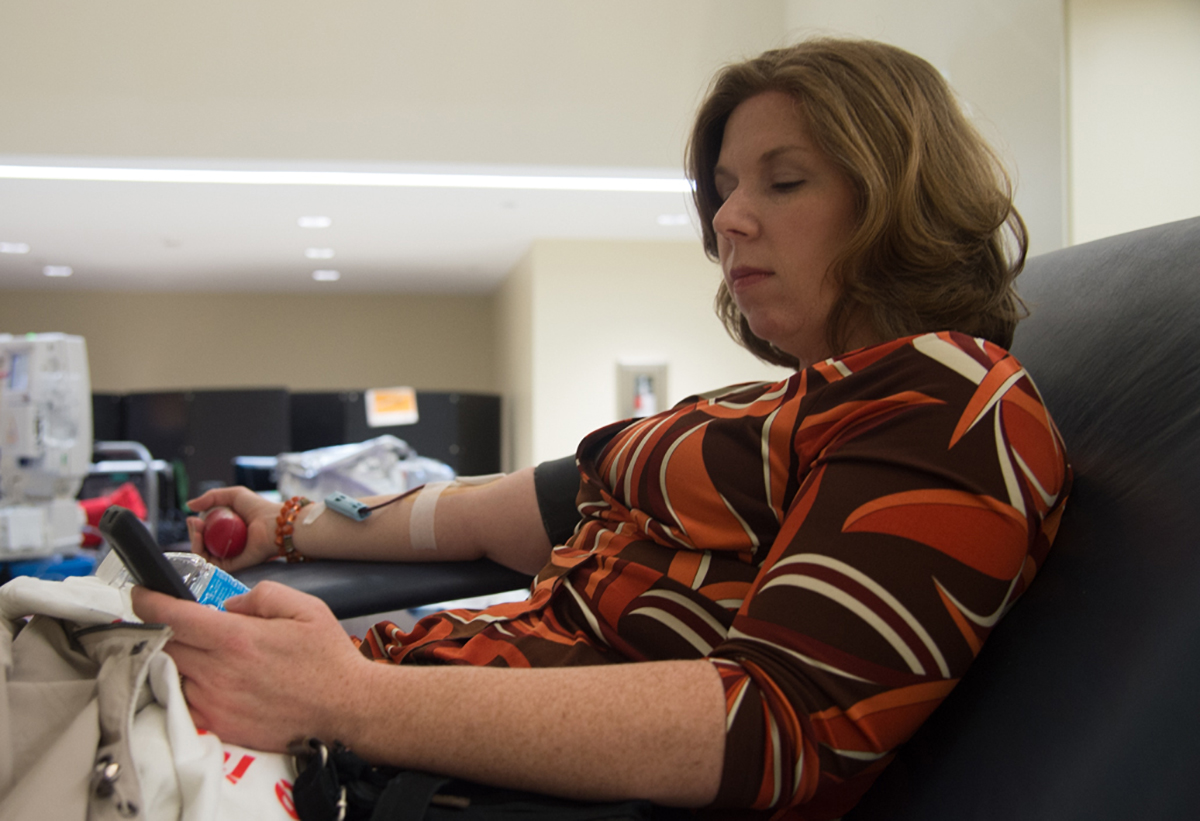 Melissa Van Meter checks messages on her phone as she gives blood on January 27, 2016. She is the Associate Director of Operations at OU Finacial Aid. (Robert McGraw/WOUB)