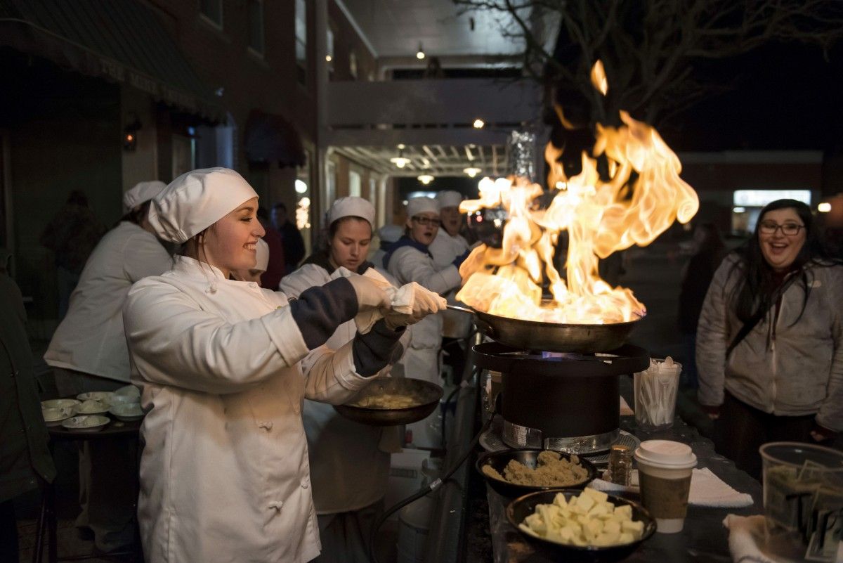 Students from the Hocking College Culinary Arts program created Bananas Foster flambé, during Final Friday on the Square, in Nelsonville, Ohio Friday night, January 29, 2016. Mackenzie flambés the sliced bananas, while adding a dash of seasoning. This years team included: McKenzie, Tiffany, Hollee, Shatiya, Mel, Zach, Dylan, Elizabeth, and Morgan. Mackenzie flambés the sliced bananas, while adding a dash of seasoning. (Margaret Sabec/WOUB)