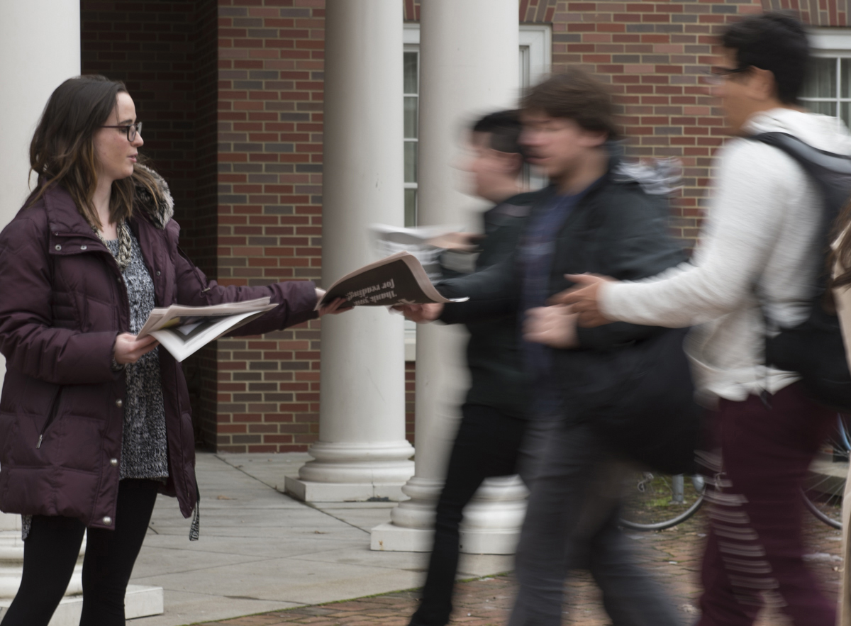 Ohio University Journalism Major and Post Editor Emma Ockerman hands out paper to people bassing by. (Robert McGraw/WOUB)
