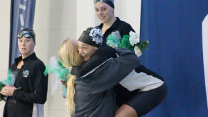Ferguson hugs a teammate after placing 2nd in the 100 fly at the 2016 MAC Championships