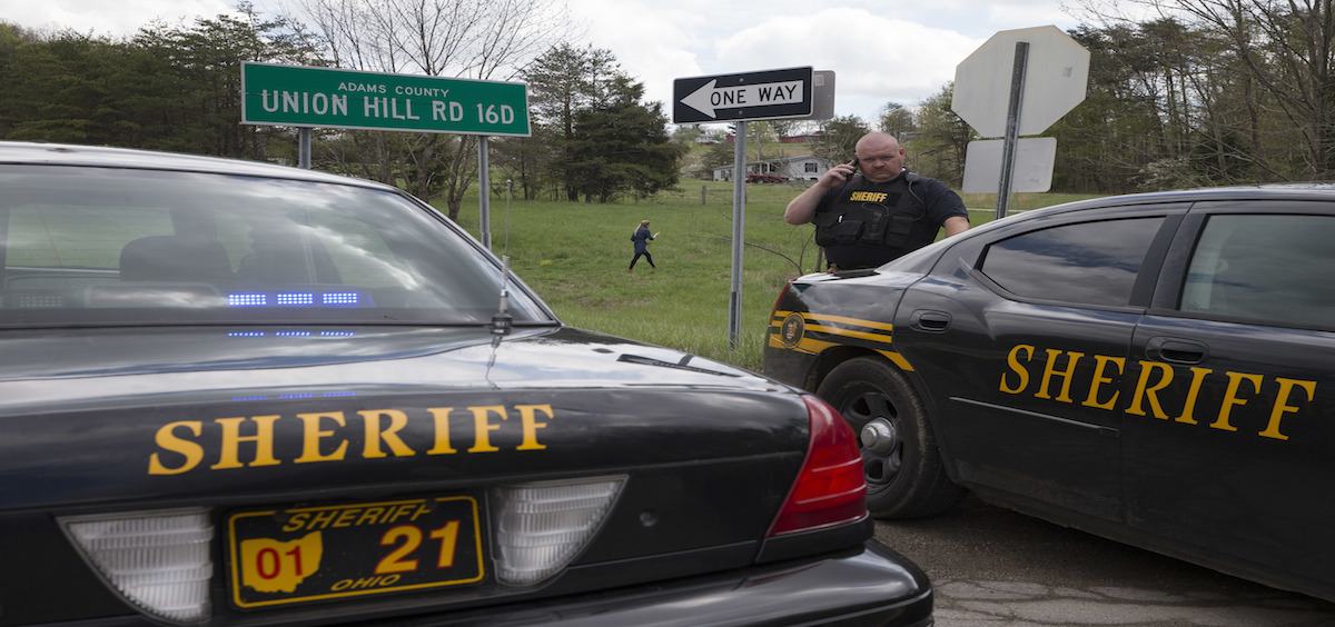 Authorities create a perimeter near a crime scene on Union Hill Rd, Friday, April 22, 2016, in Pike County, Ohio. Shootings with multiple fatalities were reported along a road in rural Ohio on Friday morning, but details on the number of deaths and the whereabouts of the suspect or suspects weren't immediately clear. The attorney general's office said a dozen Bureau of Criminal Investigation agents had been called to Pike County, an economically struggling area in the Appalachian region some 80 miles east of Cincinnati. (AP Photo/John Minchillo)