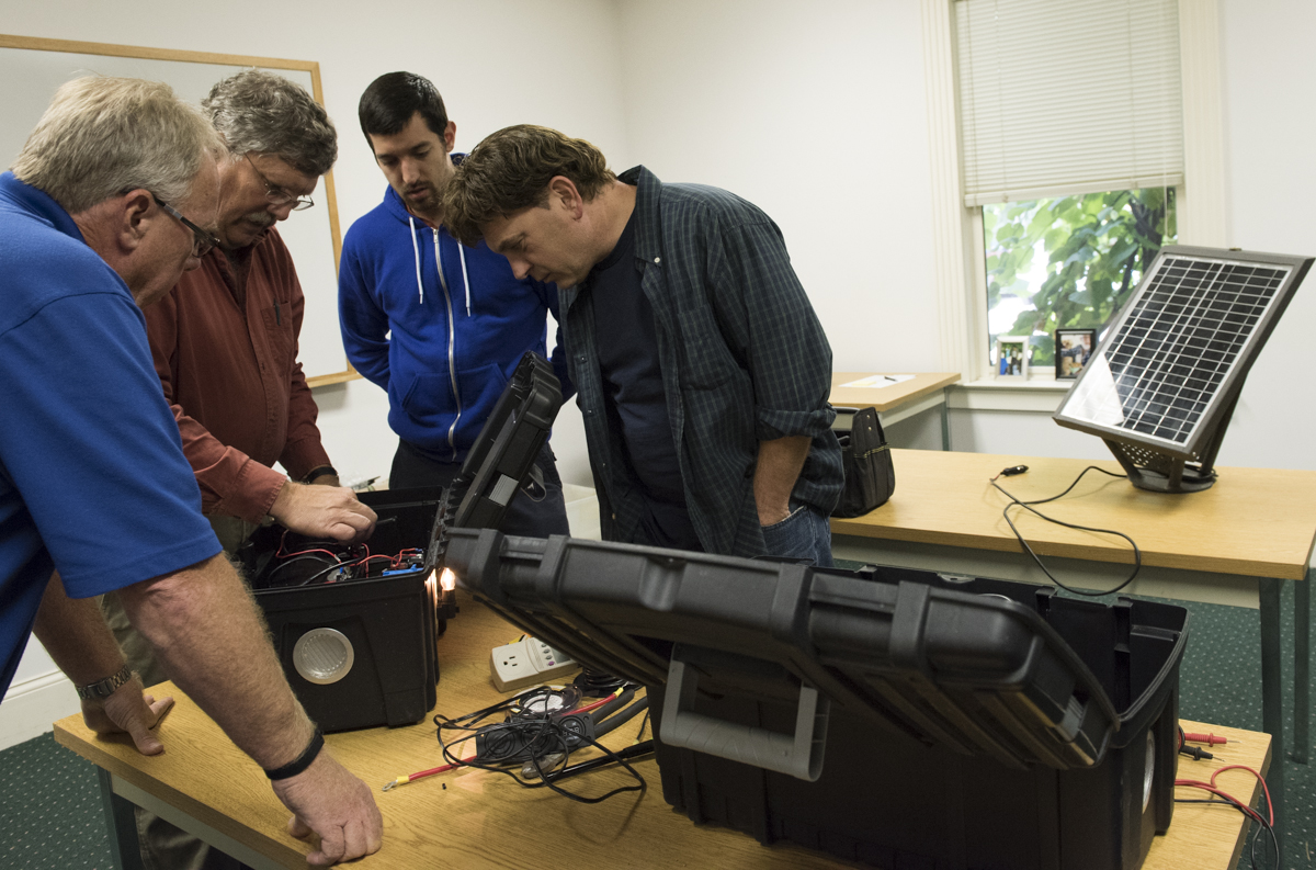 Jay Warmke, 2nd from left, shows participants Anthony Joyce, Steve Roley, and Thom Andrews how to effectively wire a solar power generator on September 28, 2016, in Athens, Ohio. (Robert McGraw/WOUB)