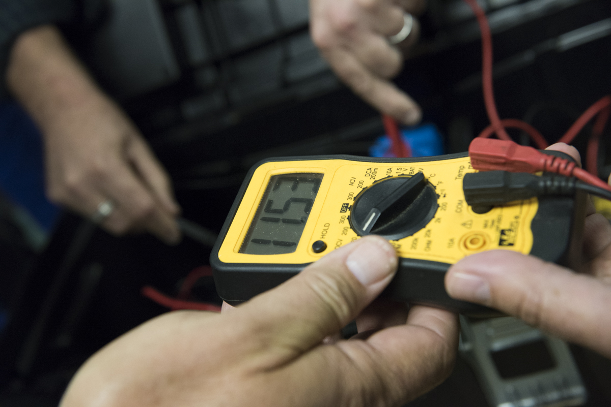 Do It Yourself workshop participants use a multi meter to test the voltage of a battery  on September 28, 2016, in Athens, Ohio..  (Robert McGraw/WOUB)