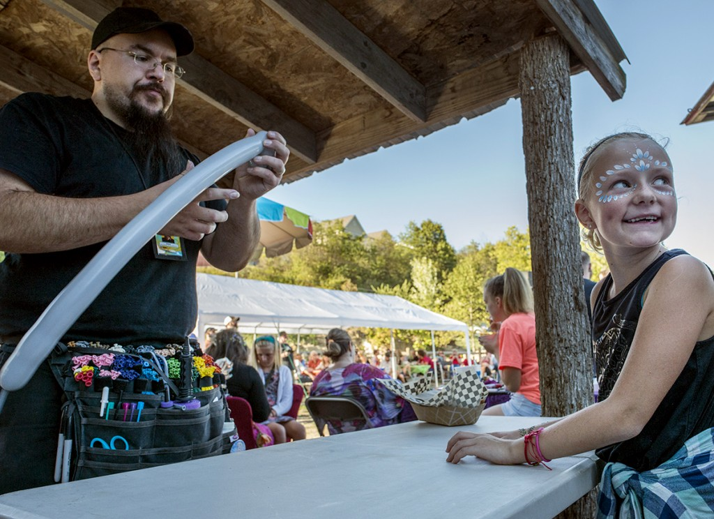 Joe from Balloosions, left, begins to construct an elephant out of balloons for Kiersten Whiteman, 8, on Sunday, Sept., 25, 2016 at the Little Fish Brewing Company in Athens, OH. At the Aydn's Dream Fundraiser, booths were set up for balloon animals, henna tattoos and face painting. (Kelsey Brunner/WOUB)