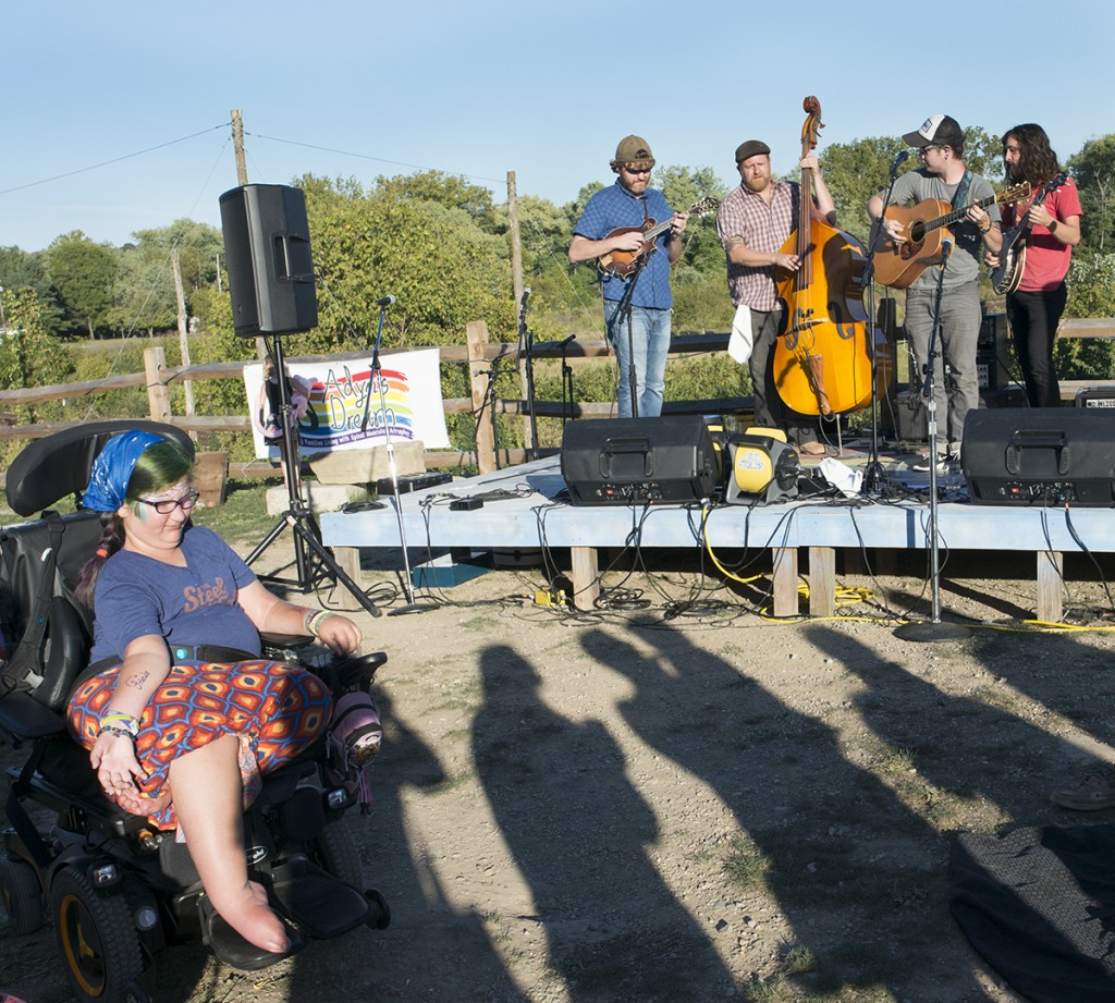 Adyn Bucher, 12, squints against the sun as Billy Strings and his band play music at her fundraiser, Adyn's Dream, on Sunday, Sept. 25, 2016 at Little Fish Brewing Company in Athens, OH. Adyn's fundraiser raises money to help family living with Spinal Muscular Atrophy in an attempt to raise money for travel expenses and needs, like wheel chair ramps. (Kelsey Brunner/WOUB)