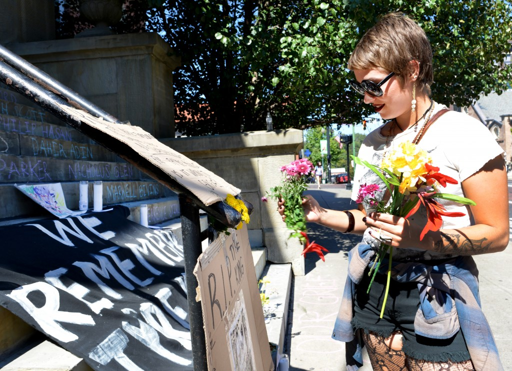 Mary Baxter puts fresh flowers around the cardboard signs that were made to honor Tyre King on Wednesday, September 21, 2016 in Athens, Ohio. Baxter collected fresh wildflowers from around town to freshen up the flowers that were wilting in the heat after being displayed since the beginning of the protest around 9 am this morning.