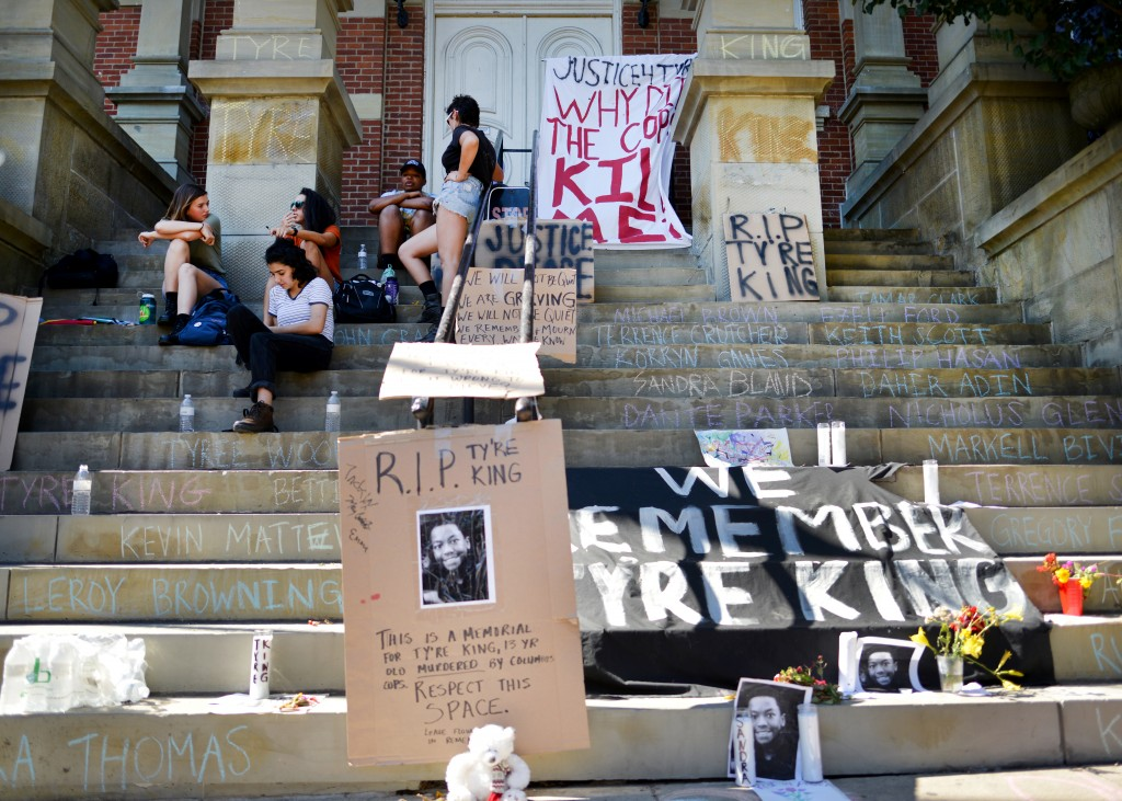 Students of Ohio University and young residents from around Athens gather on the Athens County Municipal Courthouse steps on Wednesday, September 21, 2016 in Athens, Ohio. Students made cardboard signs and chalked the courthouse steps and pillars with Tyre King's name and photograph. (Kelsey Brunner/WOUB)
