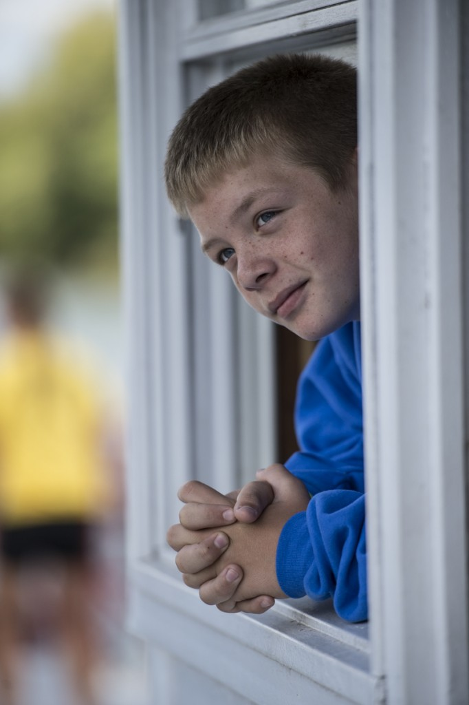 Joseph Cooke, 12, watches from the steering cabin of the P.A. Denny of how the other boats are doing during the sternwheel race. (Robert McGraw/WOUB)