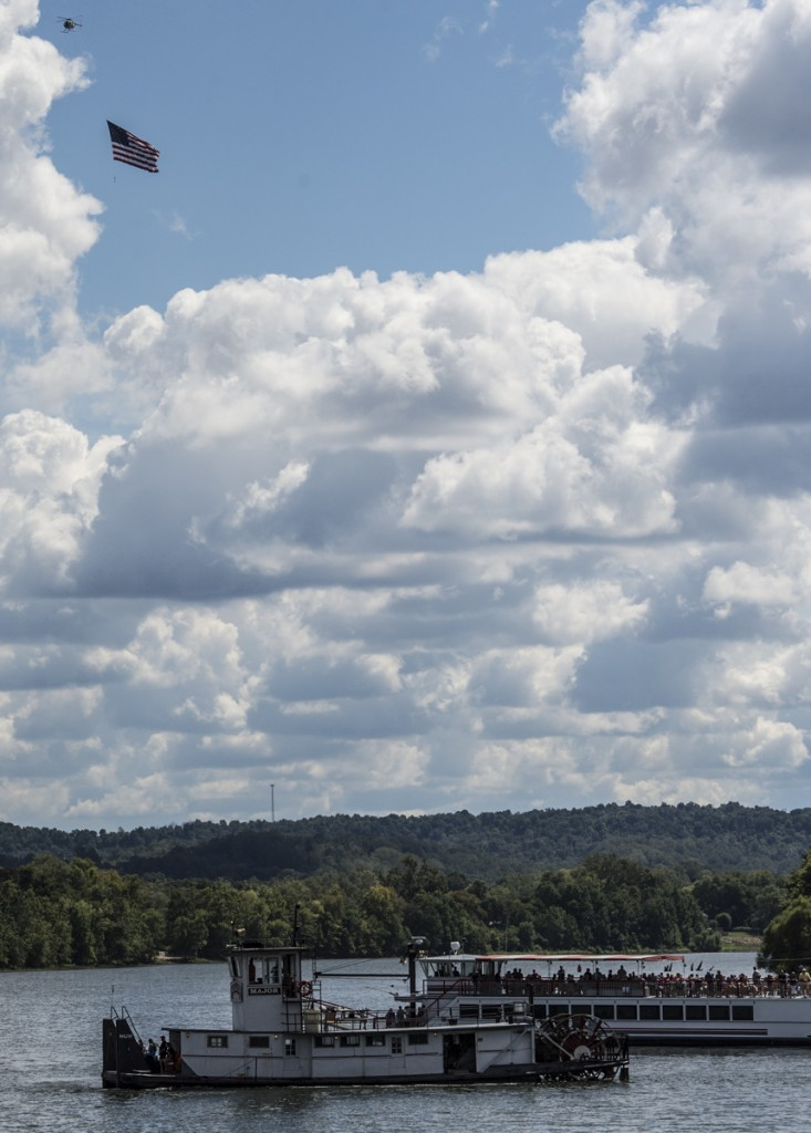 A flag is flown over the sternwheel boats by helicopter right before the start of the 2016 Sternwheel Festival Race. (Robert McGraw/WOUB)