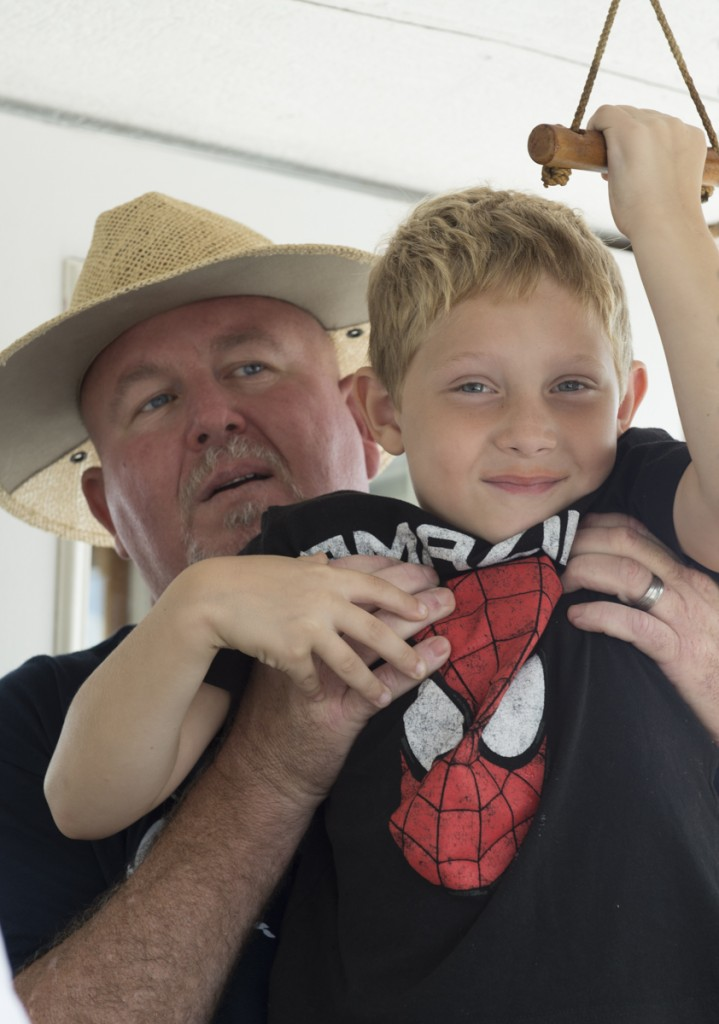 Tanner Ferguson, 6, (right) and his grandfather Scot Heckert (left) sets off the horn of the P.A. Denny announcing its completion of the race down the Ohio River. (Robert McGraw/WOUB)