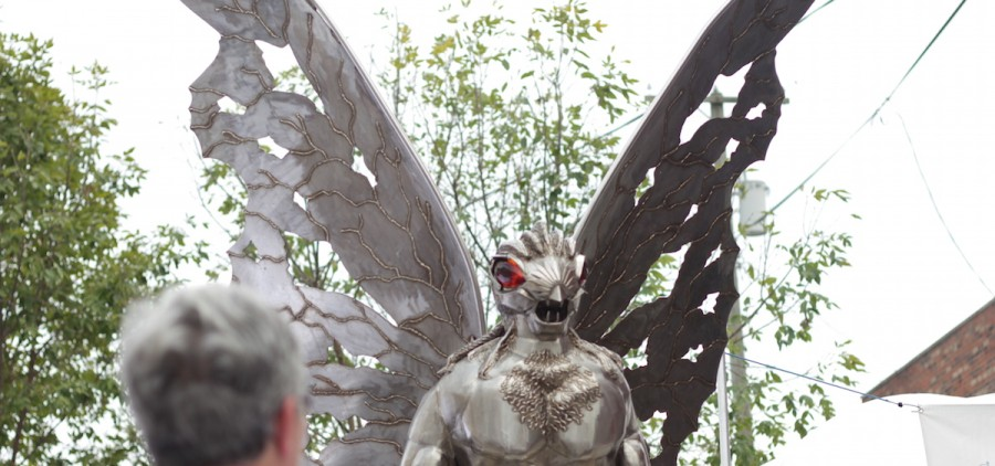 Event goers at this year's Mothman Festival in Point Pleasant, WV, gaze at the Mothman statue near the Main Street of the town. (WOUB/Joe Votaw)