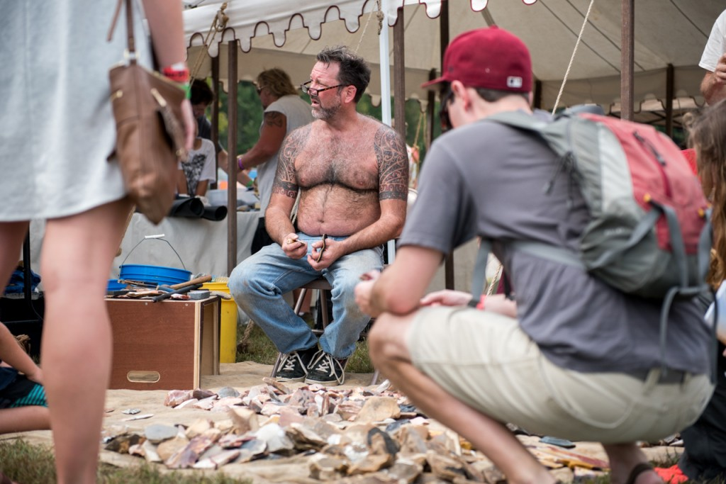 Chris Stricket, owner of The Got Rocks, making arrow heads, while festival goers look at his work at the the Ohio PawPaw Festival in Albany, OH, Sept. 18, 2016. (Carolyn Rogers/WOUB)