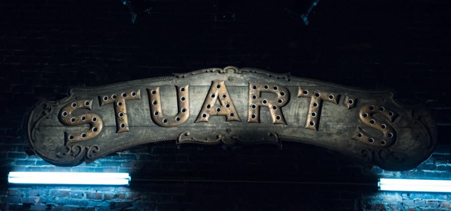 The Stuart's Opera House sign hangs from the back of the stage. While no longer able to support the lights that once lit it up, it is now lit up by lights from various angles of the stage.  (Robert McGraw/WOUB)