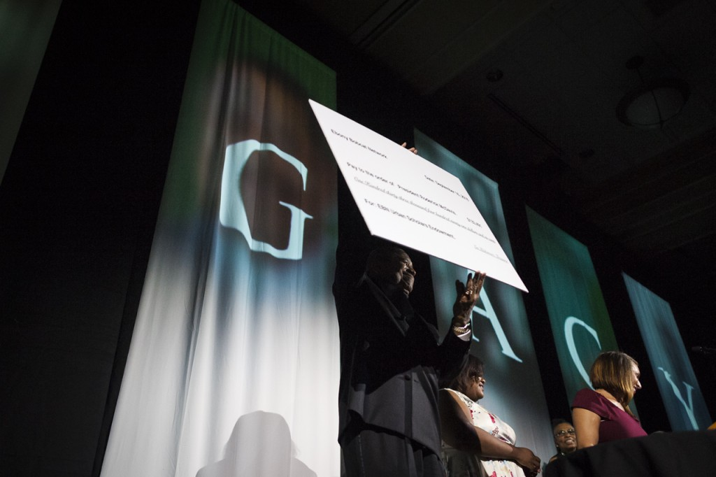 President Roderick J. McDavis holds up a check that was given for the EBN Urban Scholars Ednowment at the  Black Alumni Reunion Gala in the Baker Ballroom at Ohio University on September 16, 2016. (MICHAEL SWENSEN/WOUB)