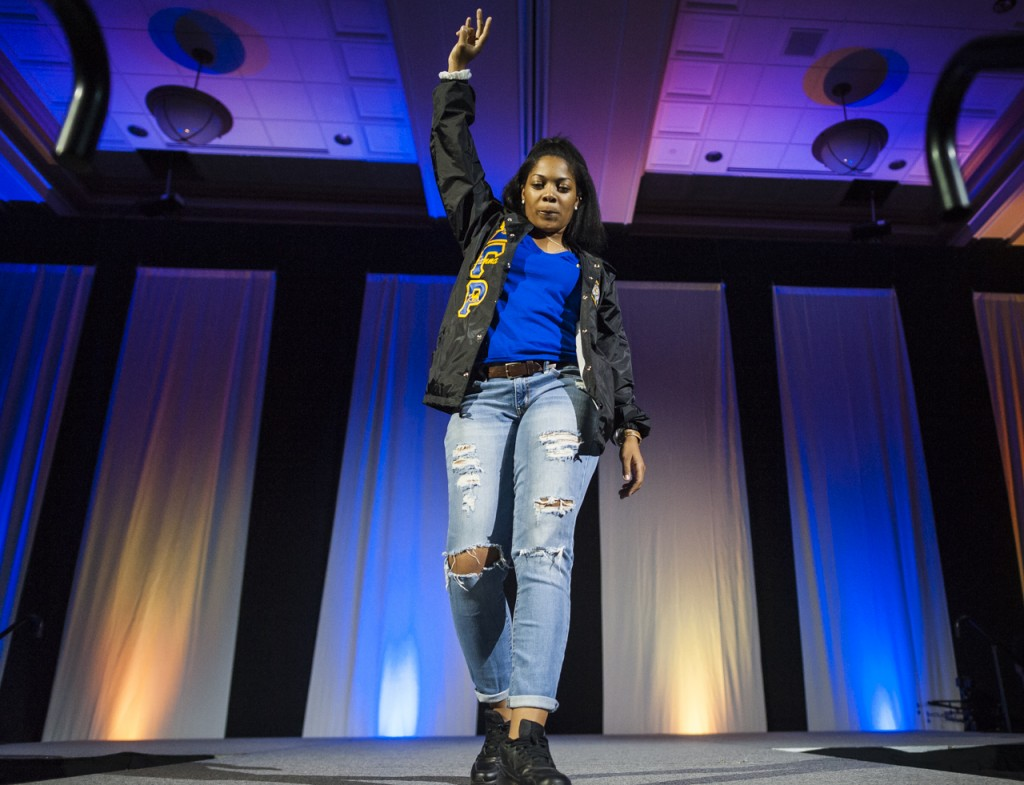 A student walks off stage holding up the symbol for her sorority at the Black Alumni Reunion Talent Show in the Baker Ballroom at Ohio University on September 17, 2016. (MICHAEL SWENSEN/WOUB)