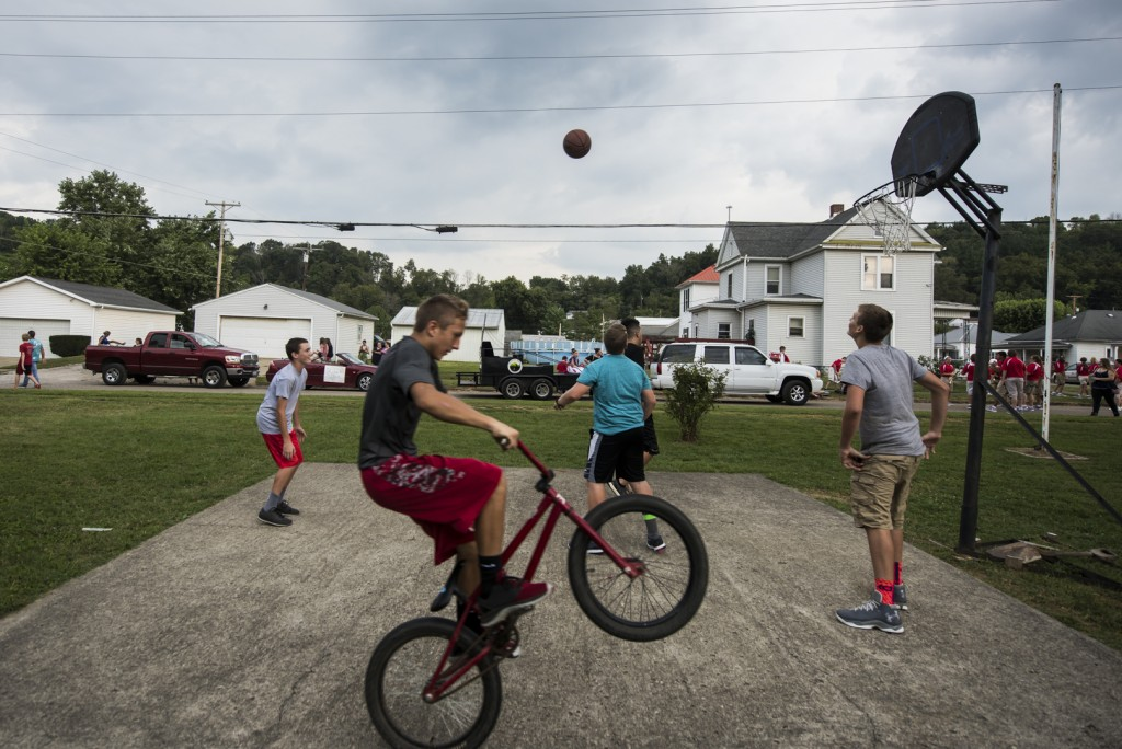 Todd Fouts, 13, from Jacksonville, Ohio, pops a wheelie on his bicycle as his friends play basketball right before the Old Settler's Reunion in Jacksonville, Ohio, on August 31, 2016. (MICHAEL SWENSEN/WOUB)