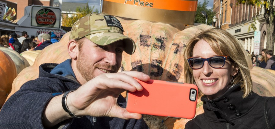 Dan Haywood, left, and Gretchen Kuhn, right, from Oakwood, Ohio, take a selfie in front of the winning pumpkin in size at the Circleville Pumpkin Show on October 22, 2016. (Robert McGraw/WOUB)