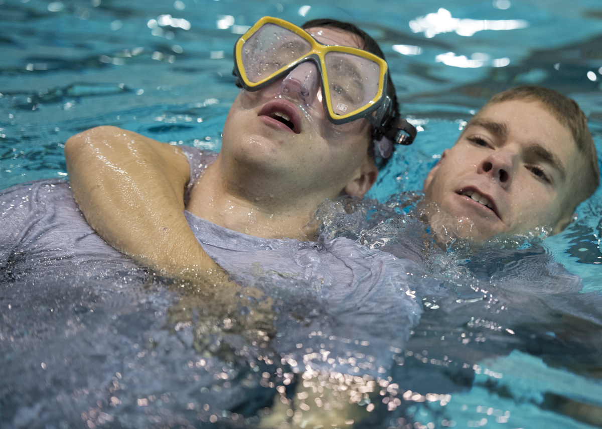 Cadet Ethan Black, left, and Cadet Dylan Hannon, right, practice saving one another during the Water Survivor Lab. (Robert McGraw/WOUB)