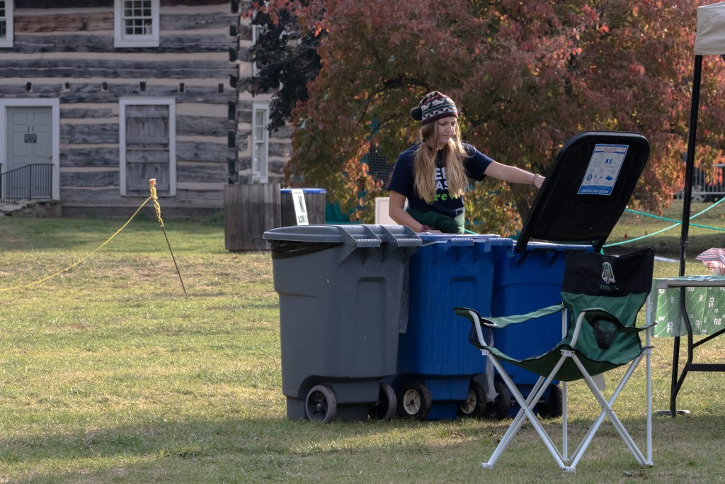Abby Miller, a Ohio University senior and recycling and zero waste events coordinator sets up the bins for the GameDay Recycling Challenge at Bingham House on Saturday, October 15, 2016 in Athens, Ohio. (Jorge Castillo Castro/WOUB)