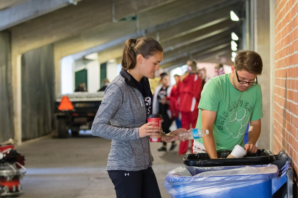 Melina Luise and MorgynFreeland, recycling and zero waste personnel and students at Ohio University set up the bins for the GameDay Recycling Challenge at Peden Stadium on Saturday, October 15, 2016 in Athens, Ohio. (Jorge Castillo Castro/WOUB)