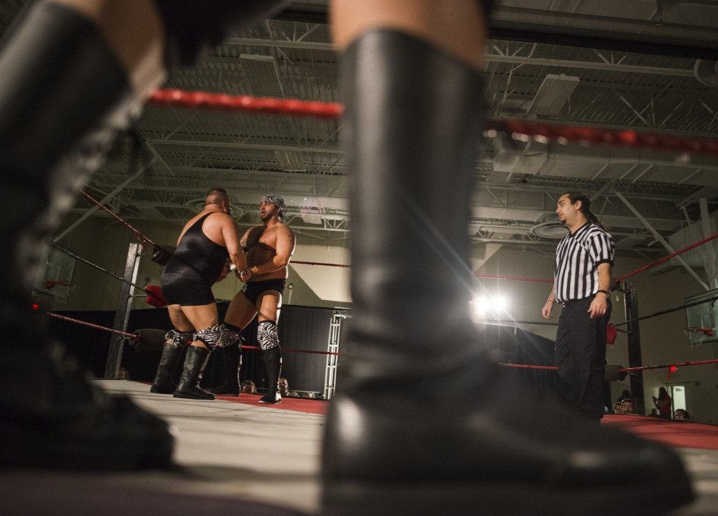 """Jock Samson, left, and partner Chris Parsons, """"Magnum CK,"""" talk before the start of a team match while referee Tim Porras walks across the ring in the student center of Hocking College during the XWE Pro Wrestling event on Friday, October 21, 2016 in Nelsonville, Ohio. Samson and Parsons are generally partners during wrestling events. (Kelsey Brunner/WOUB)"""