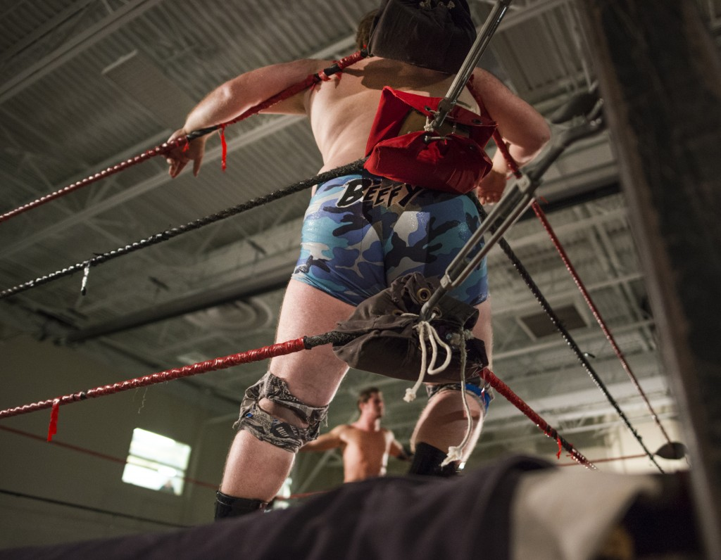 """Ben Blagg, """"Duke Beefhammer,"""" catches his breath against the corner pole of the ring while Bruce Grey addresses the boisterous crowd at the XWE Pro Wrestling event on Friday, October 21, 2016 in Nelsonville, Ohio. Grey and Blagg were the opening wrestling match of the event and prepared the crowd for the rest of the show. (Kelsey Brunner/WOUB)"""